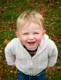 Boy smiling in Autumn. Happy boy smiling in Autumn leaves in cozy sweater Royalty Free Stock Photo
