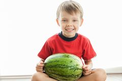 A cute boy and a big green watermelon. royalty free stock photos