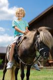 Curly boy smiling broadly while sitting on horse. Boy smiling broadly. Curly blonde-haired cute boy smiling broadly while sitting on horse stock image