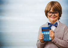 Boy smiling with calculator against blurry blue wood panel Royalty Free Stock Photography