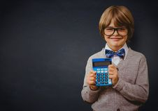 Boy smiling with calculator against navy chalkboard Stock Photos