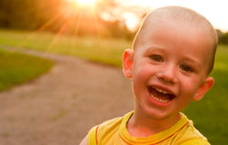 A boy smiling in the camera at sunset background Stock Photos