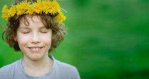 Boy smiling, with eyes closed and wreath on his head. Handsome boy with a wreath of yellow dandelions on his head closed his eyes, breathing warm air summer royalty free stock photos