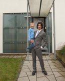 Boy is smiling on father's arm. Father and son standing in front of their house stock photography