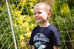 Boy smiling in front of net Royalty Free Stock Photography