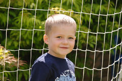 Boy smiling in front of a net Stock Photography