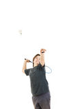 Boy smiling and holding badminton racket and trying to hit ball Royalty Free Stock Images