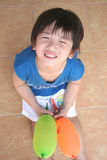 Boy smiling & holding balloons Royalty Free Stock Photos