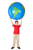 Boy smiling and holding big globe over head Royalty Free Stock Image