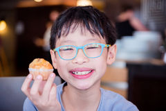Boy smiling while holding a muffin in his hand. Stock Photos