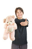 Boy smiling and holding teddy bear toy as gift Stock Photo