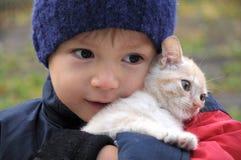 Boy smiling hugging cat Stock Image