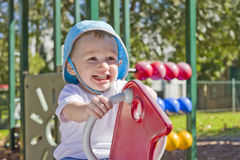 Boy smiling on playground horse. In sunshine in playground Royalty Free Stock Images