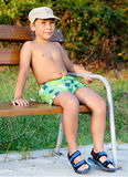 Boy smiling and sitting on bench. Little boy smiling and sitting on bench at park Royalty Free Stock Photography