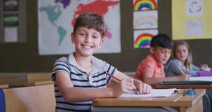 Boy smiling while sitting on his desk at school
