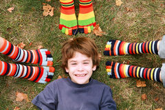 Boy Smiling Surrounded by Toe Socks. Young Boy Smiling Surrounded by Toe Socks Royalty Free Stock Image