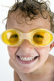Boy smiling with swimming goggles and wet hair Stock Photo