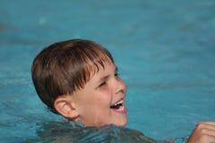 Boy smiling in swimming pool stock photo