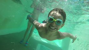 Boy smiling and swimming under water. Happy boy smiling and swimming under water stock video footage