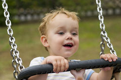 Boy smiling on swing stock images