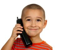 Boy smiling on telephone. Horizontal portrait of a young boy smiling while talking on a phone stock image