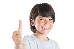 Boy smiling with thumb up. Closeup of smiling little boy showing thumb up gesture isolated on white background. Portrait of happy cute boy showing thumb up and Stock Image