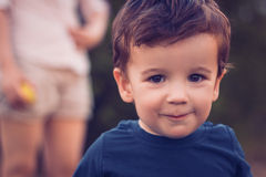 Boy smiling to a camera. With his mother in the background Stock Photo