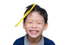 Boy smiling with yellow comb on his hair. Asian boy smiling with yellow comb on his hair over white Stock Photos