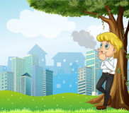 A boy smoking under the tree across the buildings Royalty Free Stock Photo