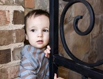Curious Boy Sneaking out of Gate to House stock photo