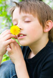 Boy sniffing yellow flower. Lovely boy sniffing yellow flower outdoors Royalty Free Stock Photography