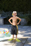 Boy (7-9) with snorkel and mask in swimsuit by swimming pool, smiling, portrait royalty free stock photo