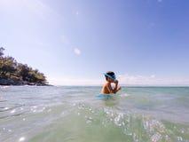 Boy snorkeler checking tube Royalty Free Stock Photos
