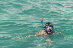 Boy with snorkeling mask diving the sea Stock Photo