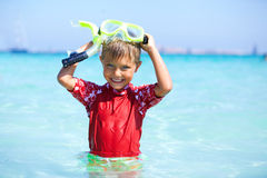 Boy snorkeling. Portrait of happy cute boy wearing snorkeling mask ready to dive in the sea Royalty Free Stock Photo