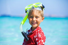 Boy snorkeling. Portrait of happy cute boy wearing snorkeling mask ready to dive in the sea Royalty Free Stock Images