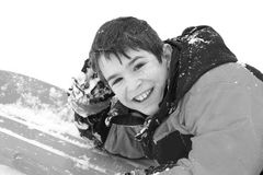 Boy in the Snow. A Boy Smiling Laying on his Sled Royalty Free Stock Photo