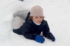 Boy in snow igloo. Biracial boy looking out from a snow igloo with snow all around him Stock Photos