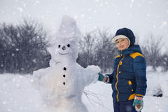 Boy with snow man stock photo