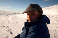 Boy in the snow mountain Stock Images