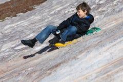 Boy snow sliding Stock Image