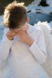 Boy in snow with white feathered wings Stock Images
