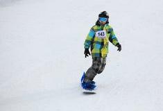 Boy snowboarding on ski slope. Arena Platos, Paltinis, near Sibiu, Romania - 2 February 2013: Arena Freestyle Open - Ski and Snowboard competition taking place Stock Photo