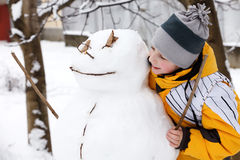 Boy and a snowman Stock Photos