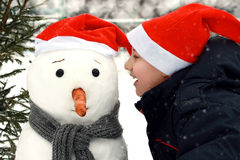 Boy and Snowman Stock Image