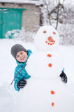 Boy and a snowman - winter holiday Stock Image