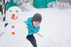 Boy and a snowman - winter holiday Stock Photography