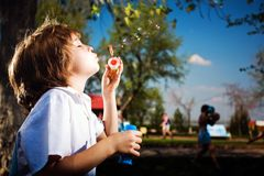 Boy with soap bubbles. In park Royalty Free Stock Image
