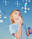Boy with soap bubbles against a sky Stock Images