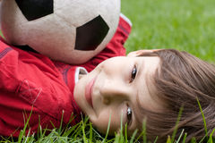 Boy with soccer ball. Happy boy lying on the grass and holding his soccer ball Royalty Free Stock Photo